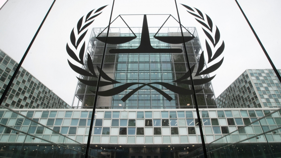 The mosaic glass facade of the International Criminal Court is seen in a photograph from street level looking up.