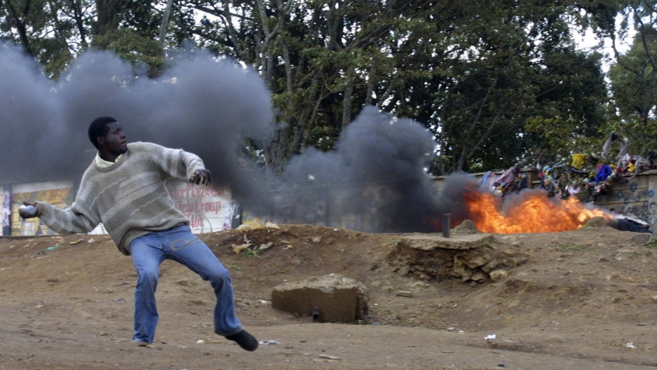 A man wearing jeans and sweater throws a rock near a fire burning outside