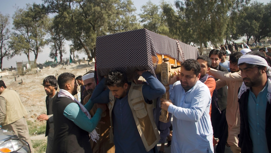 A group of men are shown carrying a casket on their shoulders drapped with a blanket.