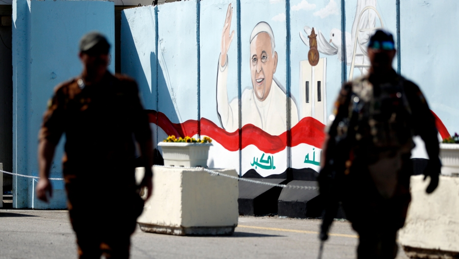 Two police officers are show in shadow in the nearground with a picture of Pope Francis on a wall in the background with the Iraqi flag painted at the bottom.