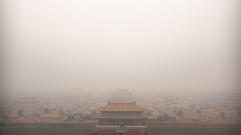 The top of a palace building in China's Forbidden City is barely viewable in a photograph showing a dense amount of smog.