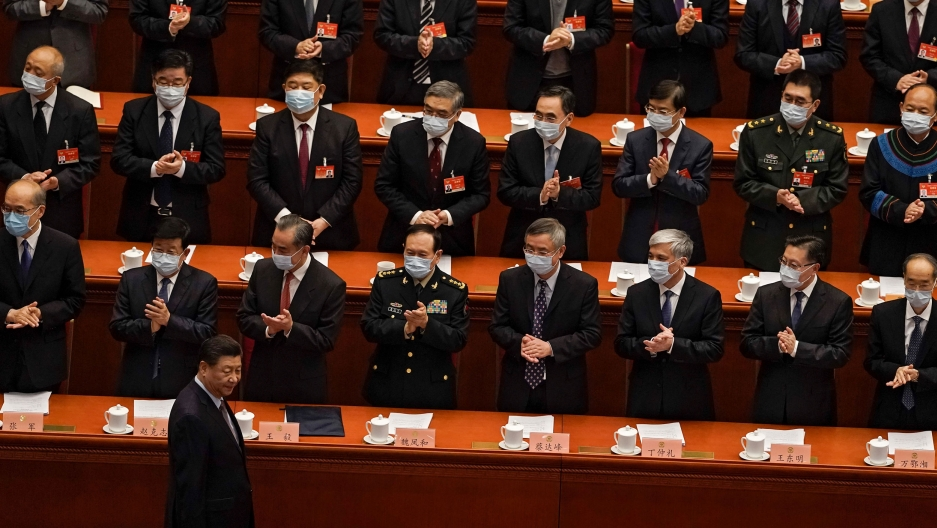 Chinese President Xi Jinping is shown wearing a dark suit and walking past several rows of men all applauding him.