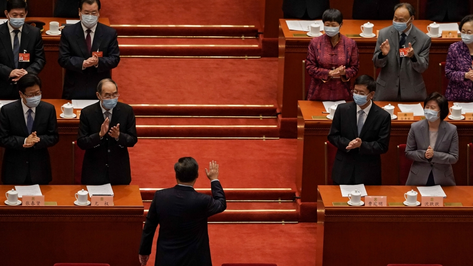 Chinese President Xi Jinping is shown with his back toward the camera and facing several rows of government officials who are clapping.