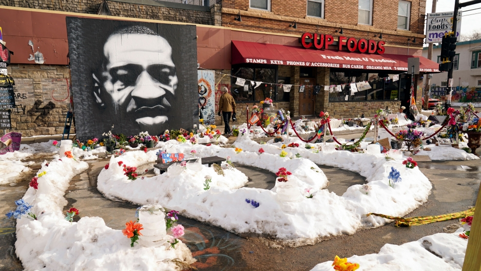A large black and white portrait of George Floyd is shown afixed to the wall of a Cup Foods store with flowers placed in snow piles.