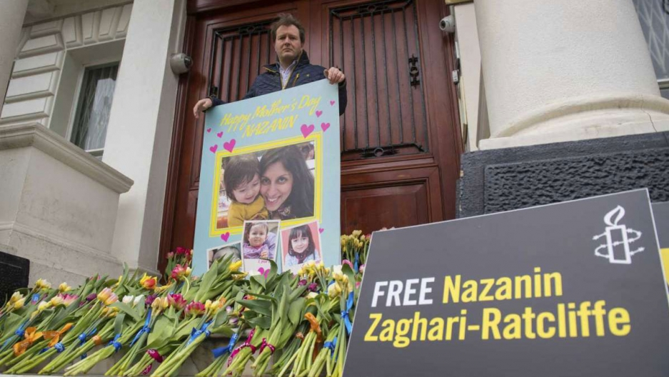 Richard Ratcliffe is shown standing in front of large wooden doors and holding a large card with a picture of Nazanin Zaghari-Ratcliffe on with with dozens of flowers nearby.