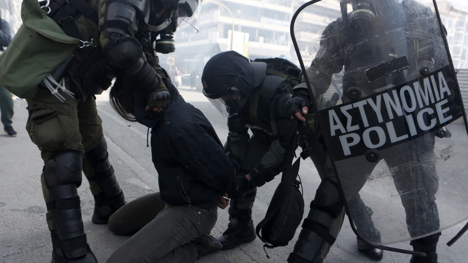 Riot police detain a man during clashes in the northern city of Thessaloniki, Greece, March 11, 2021.