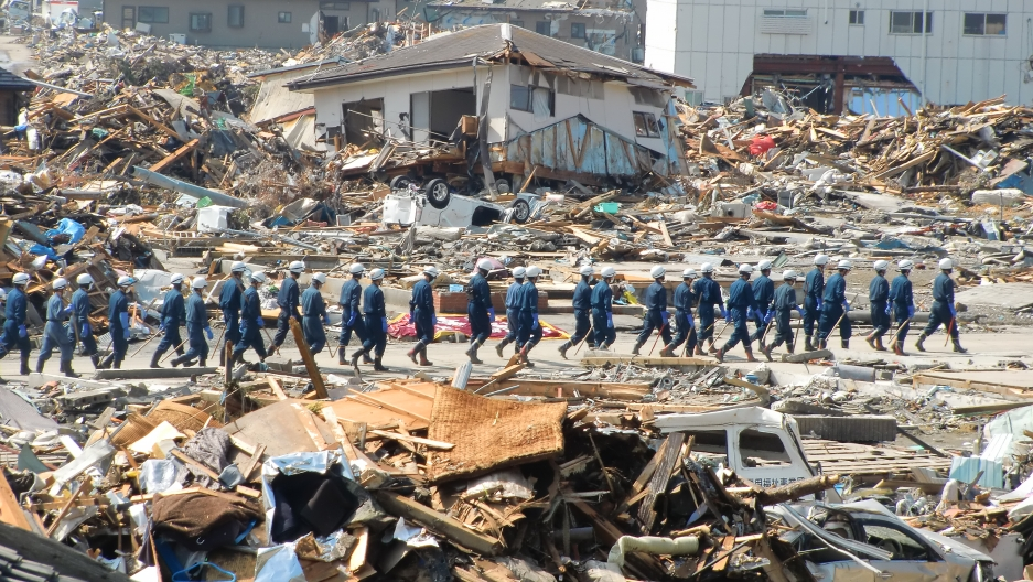 A long line of Japan's Self Defense Forces are shown wearing blue protective outfits and walking among the rubble of Ishinomaki.