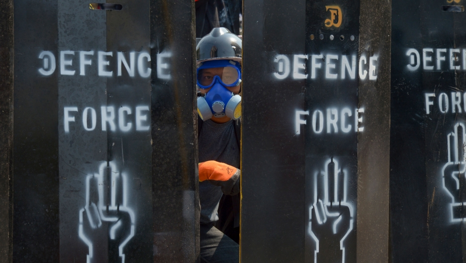 A person wearing an air-filtration mask and helmet is show looking through makeshift metal barriers with the words 'Defense Force' and a hand holding up three fingers painted on them.