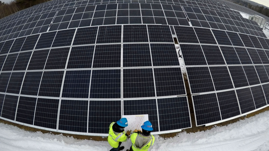 Several rows of large solar panels are shown with a wide angle lens with two people at the bottom of the photo wearing yellow safety vests and hard hats.
