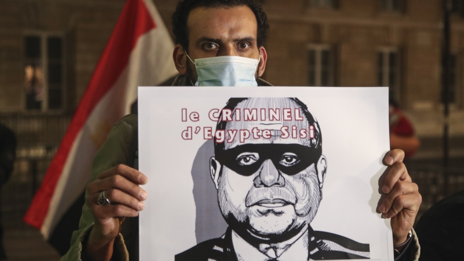 A man holds a placard depicting Egyptian President Abdul Fattah al-Sissi and reads he is a criminal as he stages a protest by the National Assembly in Paris, Dec. 8, 2020.
