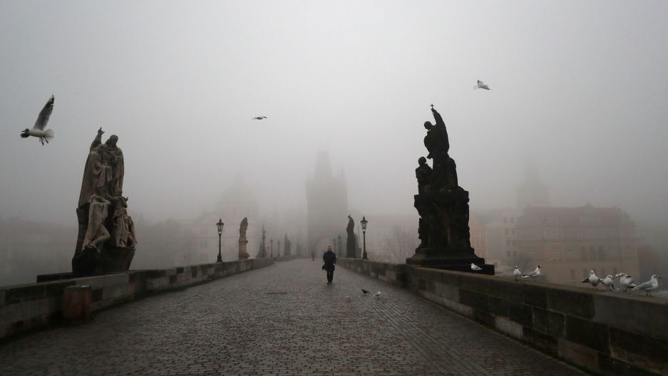 A cloudy, gray day is shown from one end of the Charles Bridge, with several stone statues on either side and a man walking in the distance.