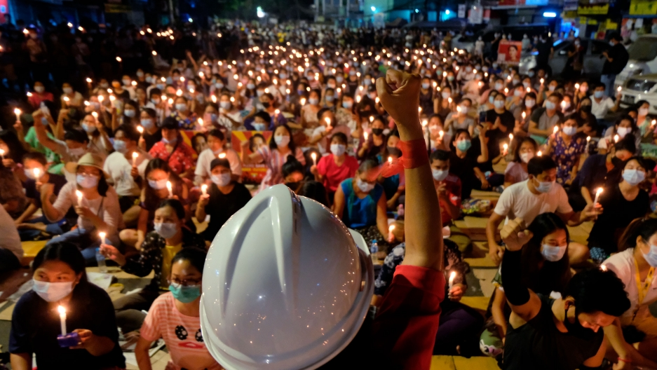 A person is shown in the near ground with their fist in the air and wearing a white construction helmet with a large crowd of people sitting and holding candles.