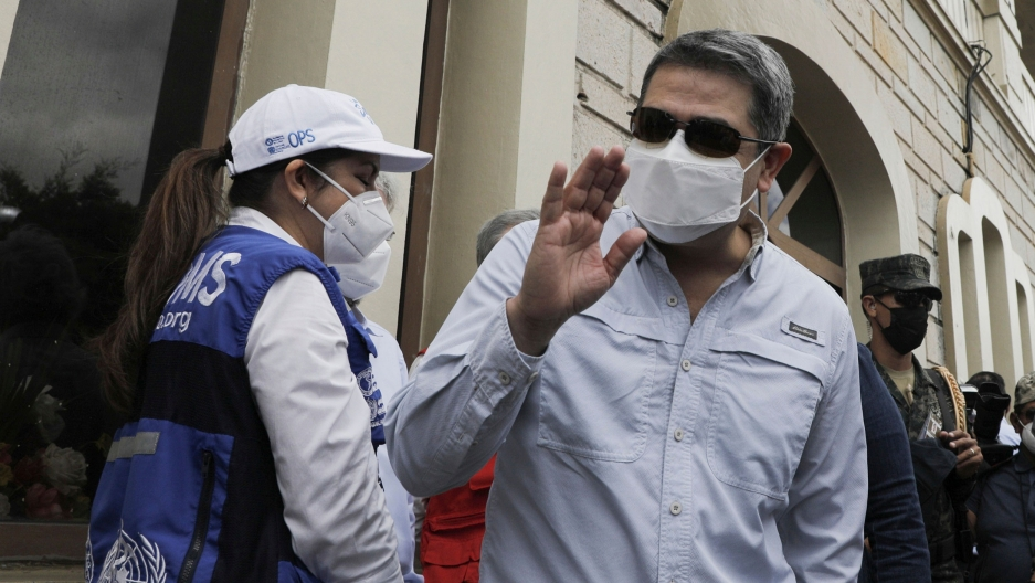 Honduran President Juan Orlando Hernandez is shown wearing a medical mask and sunglasses while waving his right hand.
