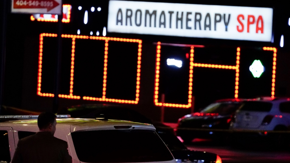 A police SUV is shown in the nearground with a bright white sign in the distance for an Aromatherapy spa.