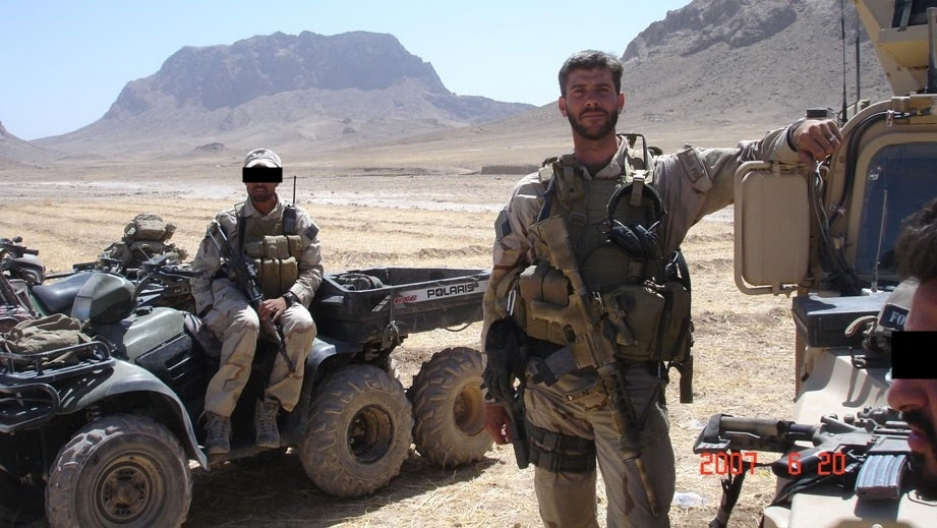 A soldier in uniform stands next to a man in a military vehicle with rugged mountains in the background.
