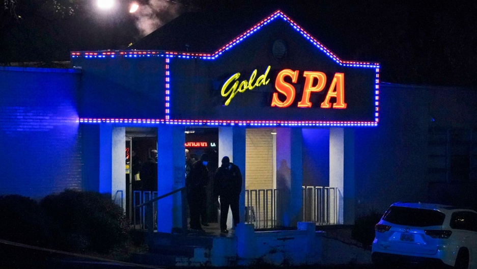 The front door of a spa is shown lit with blue colors and a sign above the entrance with the name, Gold Spa in neon lighting.
