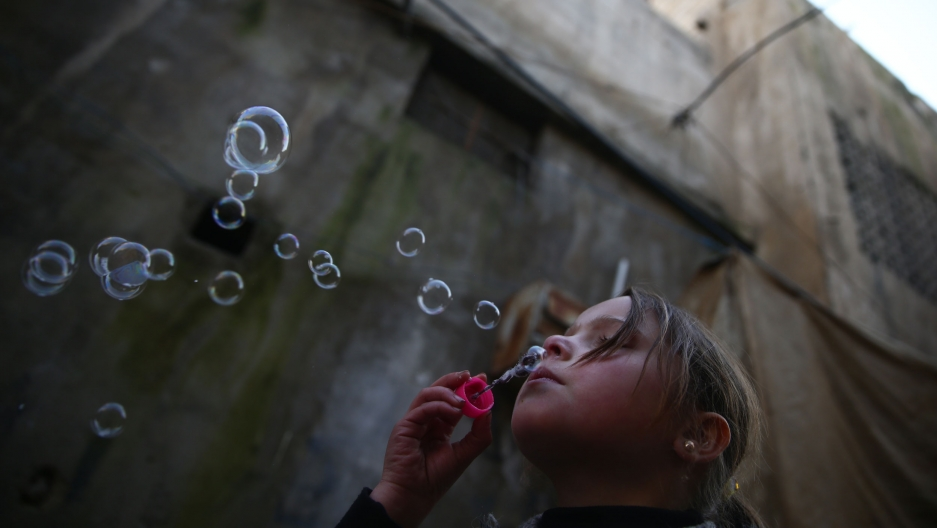 A young girl blows bubbles in the Douma neighborhood of Damascus, Syria, Jan. 19, 2017.