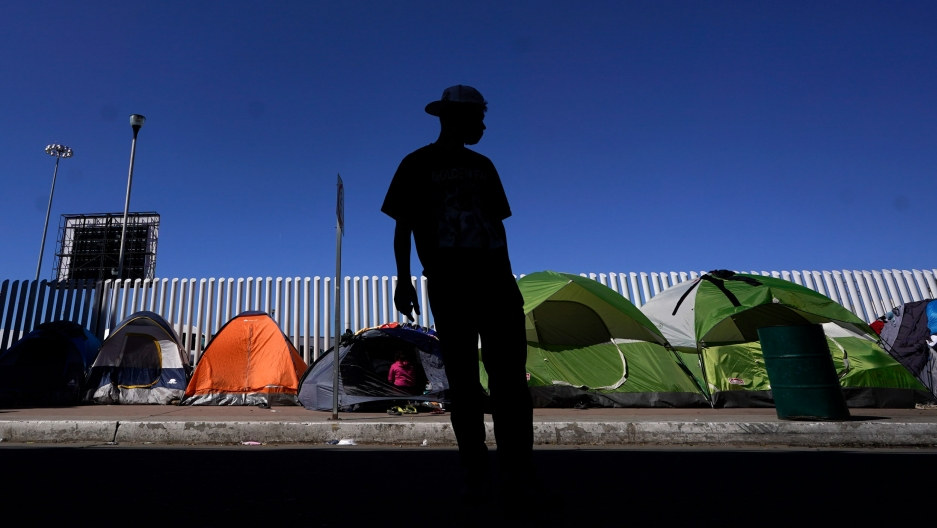 A man is shown in shadow and wearing a brimmed hat with several pup tents shown in focus in the background.