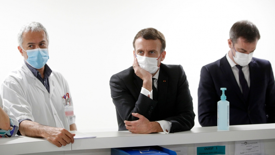 French President Emmanuel Macron is shown wearing a dark suit and white face mask while flanked by other officials.