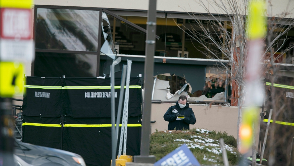 A police officer is shown wearing a face mask amidst broken glass and other remnants of a shooting with Boulder Police baracades in the nearground.