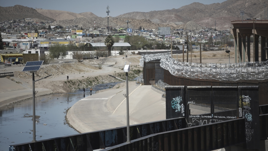 People cross the border between US and Mexico