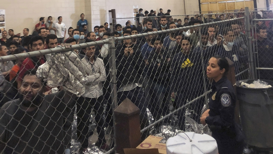 A group of men stand behind a fenced area within a detention center at the border.