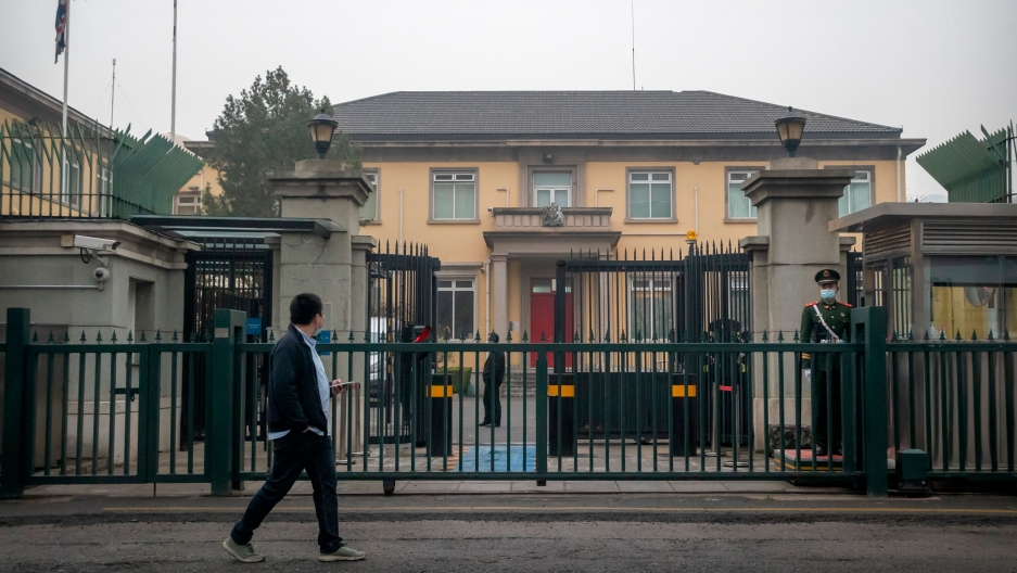 The British Embassy is shown in the distance through a closed metal gate with a Chinese paramilitary police officer standing guard.