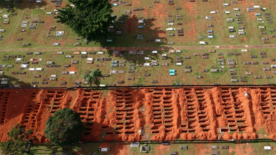 A cemetery is shown via an ariel view with several rows of empty new graves and exposed dirt.
