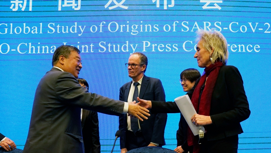 Marion Koopmans (R)is shown holding a folded white paper and reaching out to shake the hand of Liang Wannian.