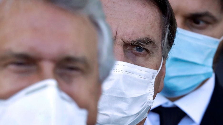 Brazilian President Jair Bolsonaro is pictured in a close up photograph showing only his face covered by a medical face mask.
