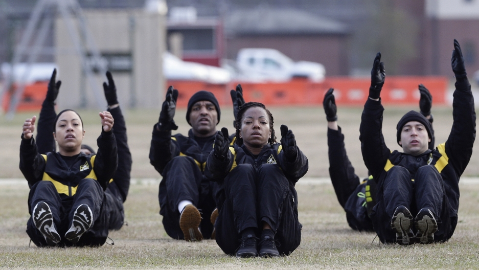 Military men and women exercise in a field.