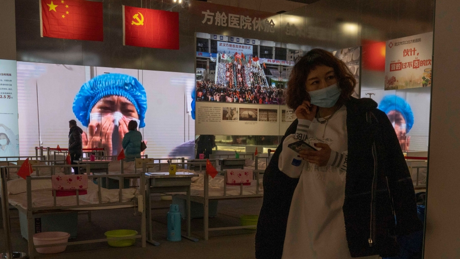 A woman is shown holding a mobile phone and wearing a face mask with an image of a medical worker on display in the background.
