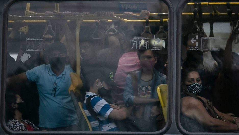 A crowd of people are shown crammed onto a bus as shown through the window.