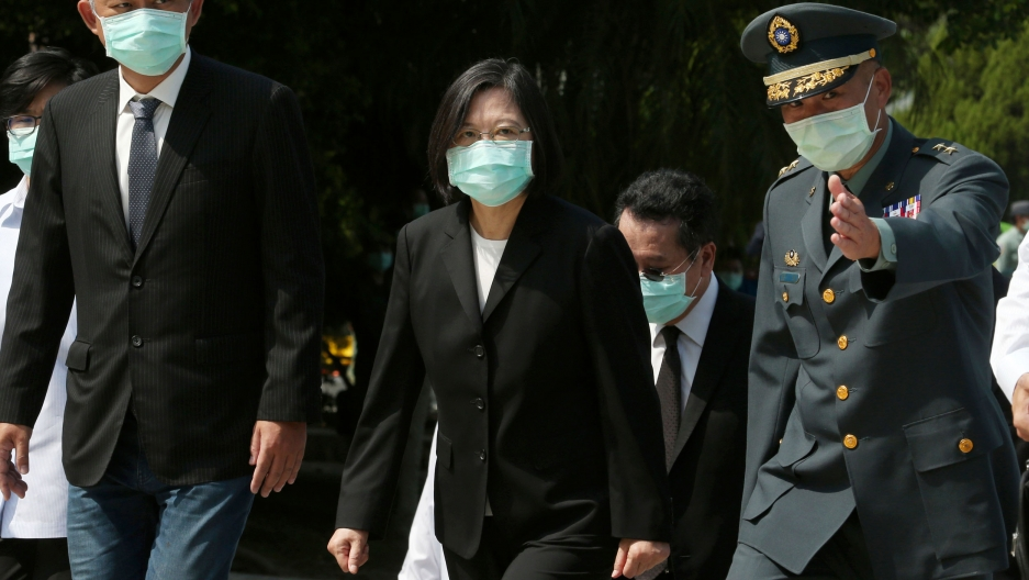 Taiwan's President Tsai Ing-wen is shown wearing a dark suit and walking while flanked by a military officials to her left.