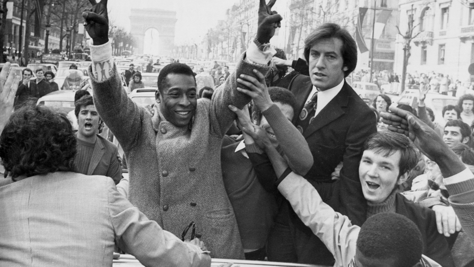 Pele standing and flashing a victory sign, surrounded by happy French people, in Paris