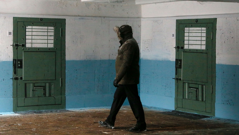 A person wearing a jacket with a hood up is shown walking past a wall with two prison doors painted on it.