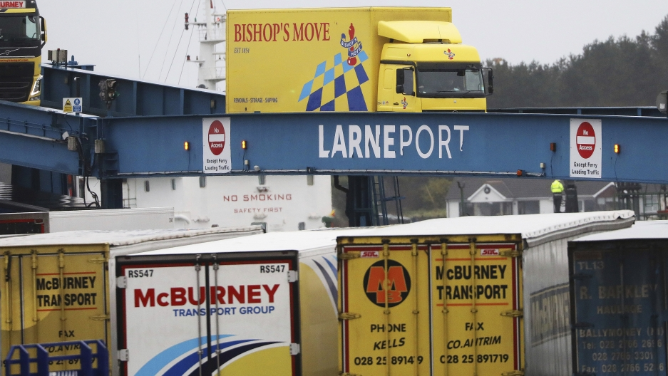 Blue, yellow, and white vehicles disembark from a ferry arriving from Scotland.