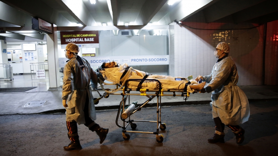 Health care workers of the public Mobile Emergency Service bring a patient suspected of suffering from COVID-19 to the Base Public Hospital in Brasilia, Brazil, Wednesday, March 31, 2021.