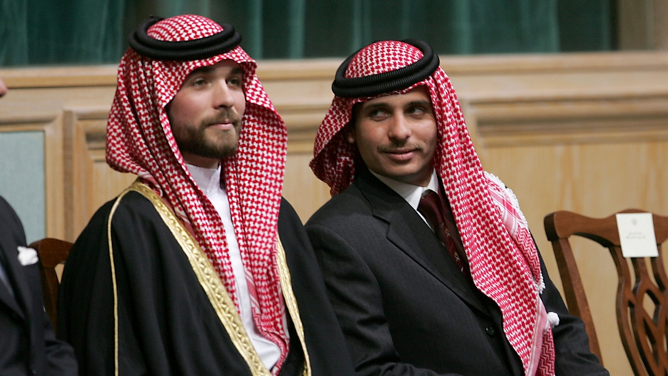 Prince Hamzah Bin Al-Hussein (R) and Prince Hashem Bin Al-Hussein (L) are shown sitting and wearing traditional red and white headscarves