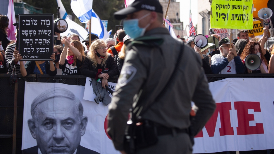 A large crowd of people are shown with several holding a banner showing Israeli Prime Minister Benjamin Netanyahu's face.