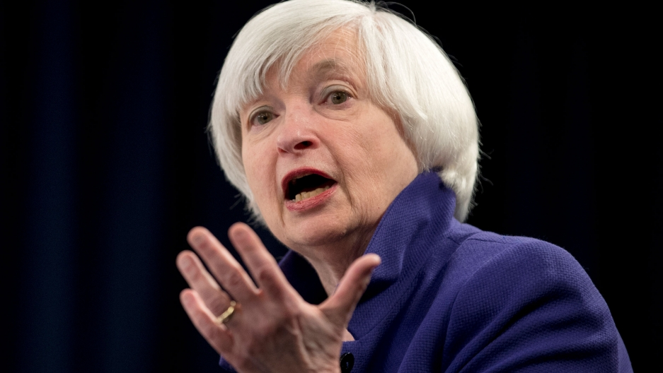 Janet Yellen is shown in a close up photograph speaking with her left hand raised palm up.