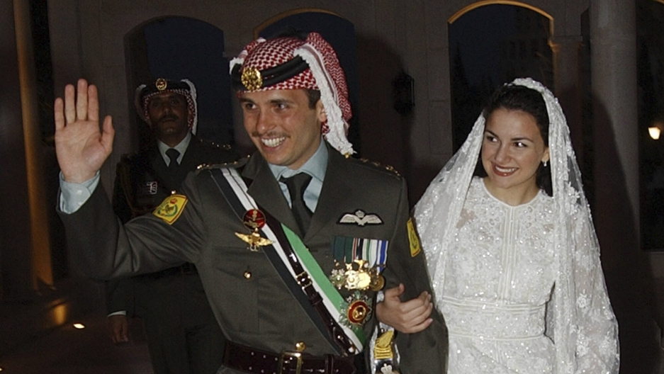 Prince Hamzah waves, wearing a military uniform walks with his bride, Prince Noor, wearing a white wedding dress and they both smile.
