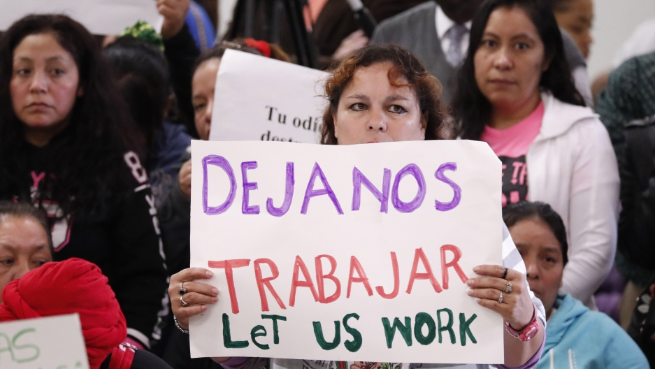 "An attendee at the House Homeland Security Committee field hearing at Tougaloo College in Jackson, Mississippi, holds a sign written in English and Spanish, stating ""Let us work,"" Thursday, Nov. 7, 2019."