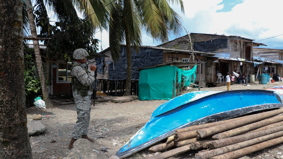 A soldier on patrol in a neighborhood with a boat on the street.