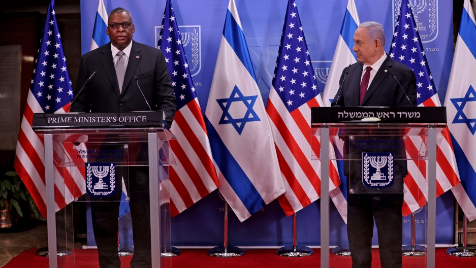 US Defense Secretary Lloyd Austin and Israeli Prime Minister Benjamin Netanyahu are shown each standing behind podiums with US and Israeli flags in the background.