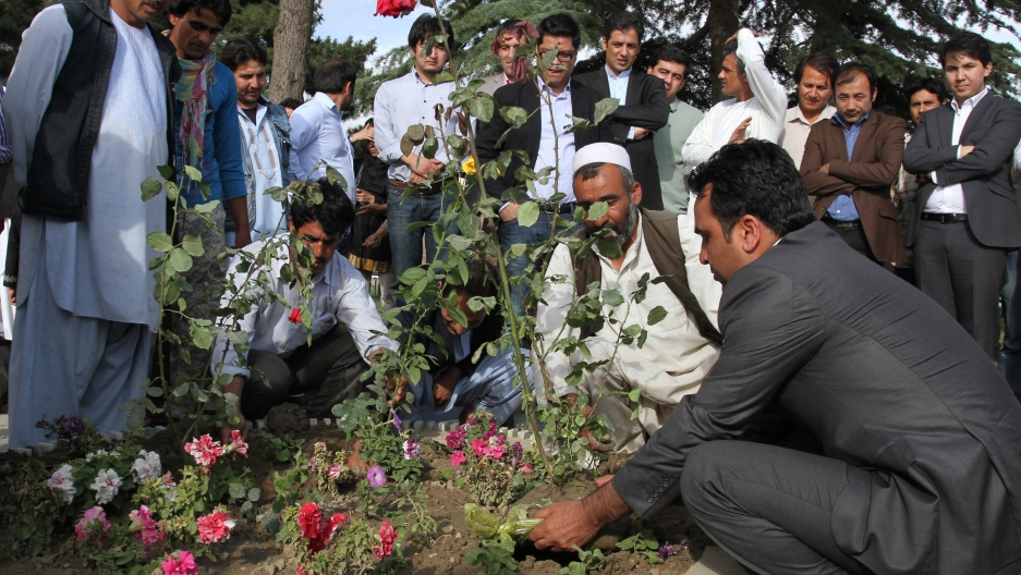 A group of men gather around a memorial to plant flowers for victims of a militant attack.