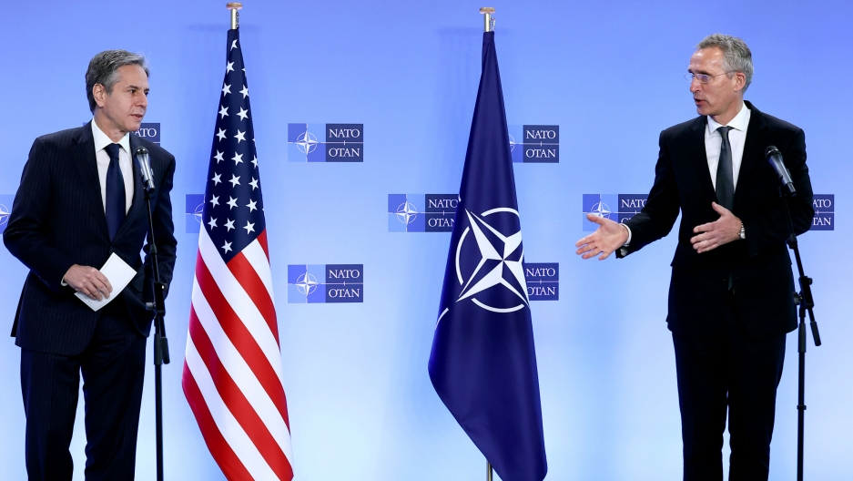 NATO Secretary General Jens Stoltenberg (R) and US Secretary of State Antony Blinken are shown standing opposite each other with the US and NATO flags in the background.