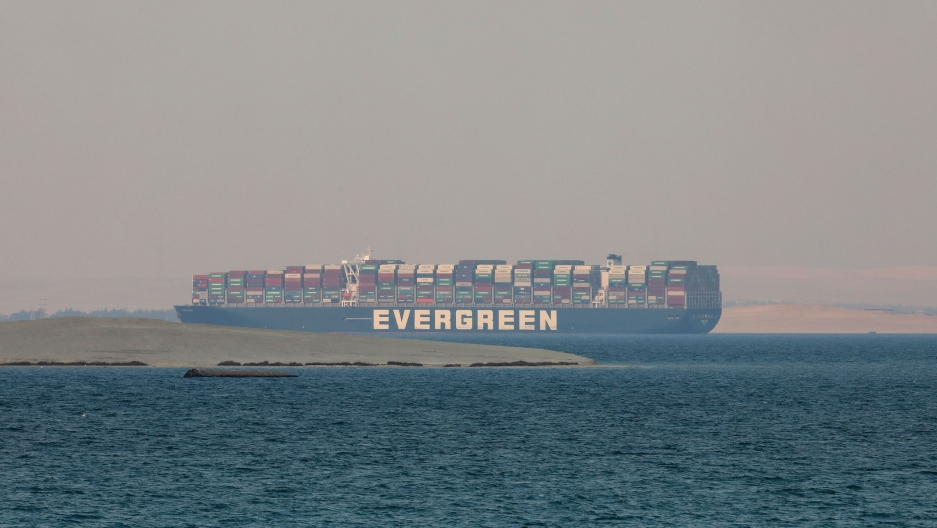 The massive cargo ship, the Ever Given, is shown in the watery distance stacked with containers.