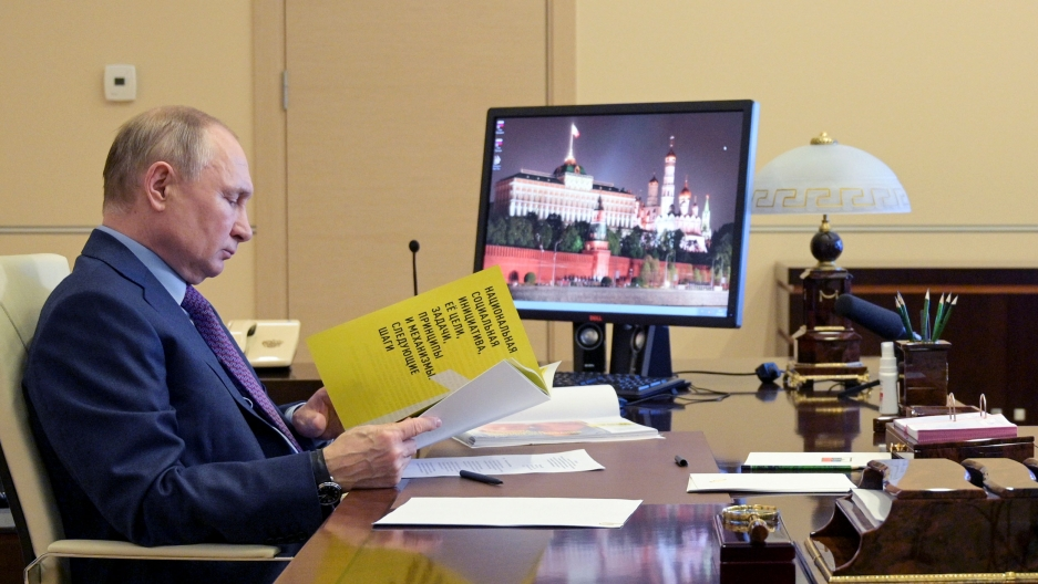 Russian President Vladimir Putin is shown sitting at a desk and looking down at a yellow document.