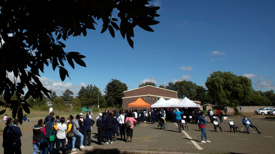 A long line of people are shown outside in a pkarking lot with an orange tent in the distance.